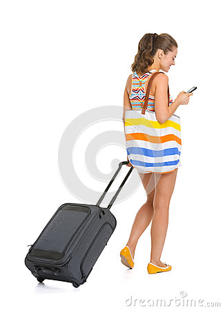 Young tourist woman with wheel bag writing sms. rear view
