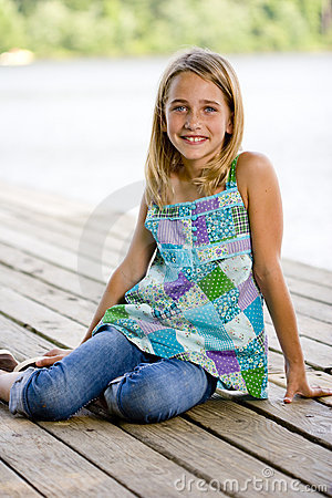 Free Young Tween Girl Sitting On A Pier Royalty Free Stock Image - 15842646