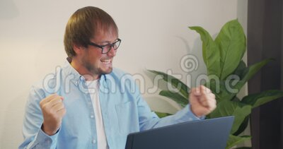 Young urban professional successful business man receiving good news in business. Success and achievement - happy. Businessman celebrating looking at laptop stock footage