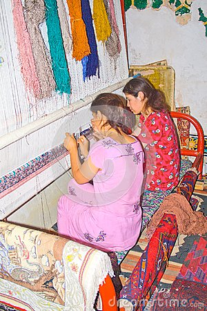 Young Uzbek girls weave carpet Editorial Stock Image