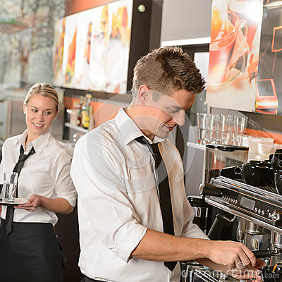 Young waiter and waitress working in bar