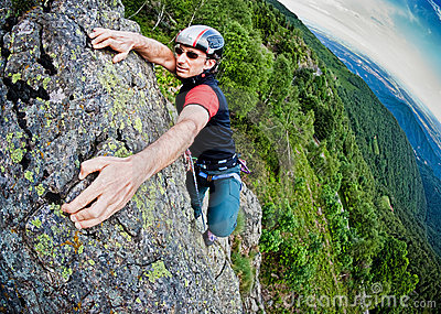 Young white man climbing a steep wall