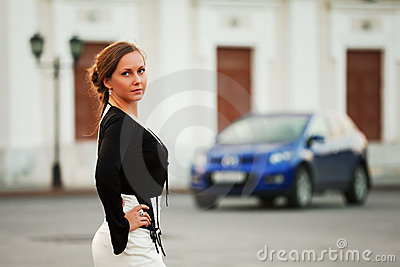 Young woman against a car parking
