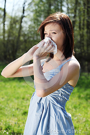 Young woman with allergy wiping her runny nose