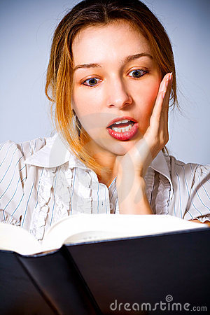 Young woman amazed by what she is reading