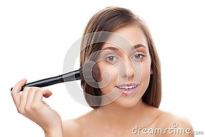 Young woman applying blusher