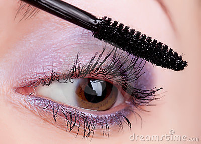 Young woman applying cosmetics on eyelashes