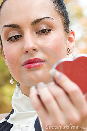 Young woman applying cosmetics on her lips