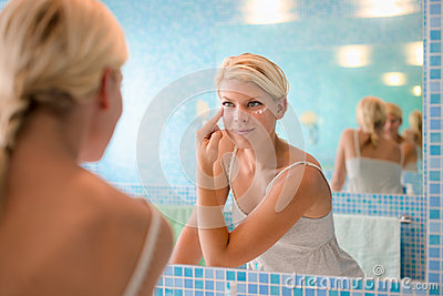 Young woman applying lotion on face at home