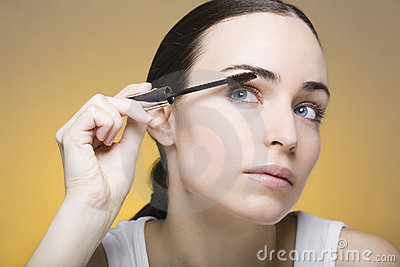 Young woman applying mascara on her self
