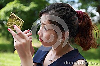 Young woman applying mascara using lash brush