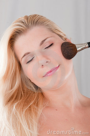 Young woman applying powder with a brush