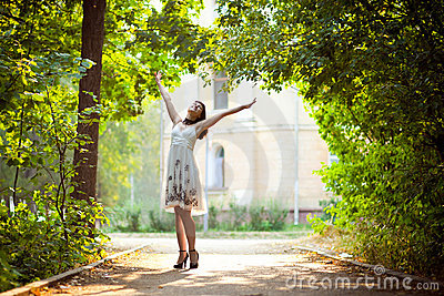 Young woman arms raised enjoying the fresh air in