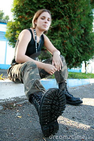 Young woman in army boots and camouflage