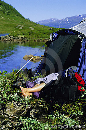 Young woman asleep in tent next to lake