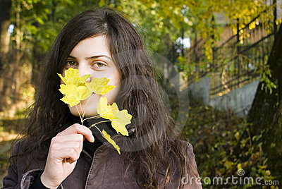 Young woman and an autumn leaf