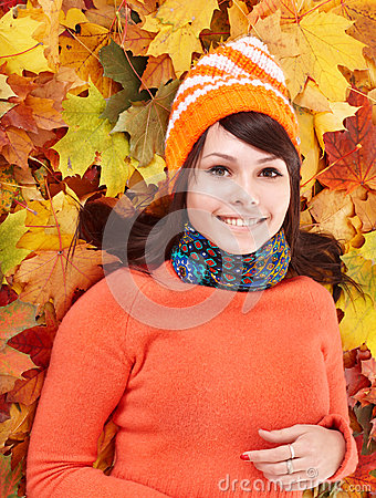 Young woman in autumn orange leaves.