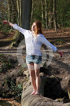 Young woman balancing on tree trunk with arms outstretched