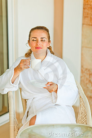 Young woman in bathrobe enjoying cup of coffee
