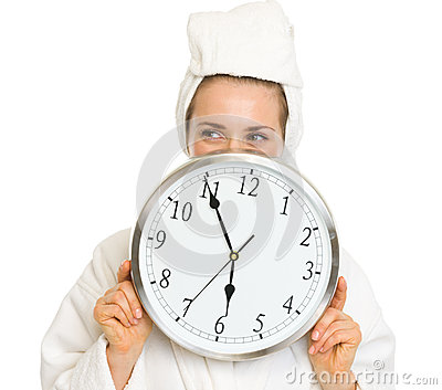 Young woman in bathrobe hiding behind clock