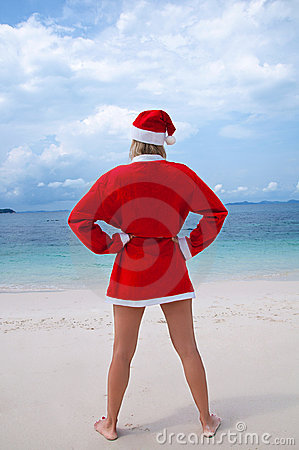 Young woman on the beach in santa s costume