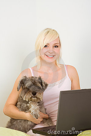 Young woman in bed with laptop and schnauzer dog