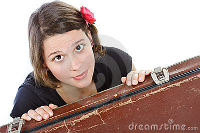 Young woman behind suitcase