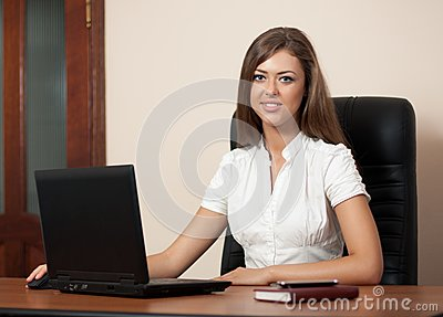 Young woman behind a table with the laptop