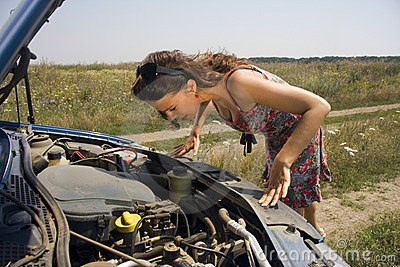 Young woman bent over engine