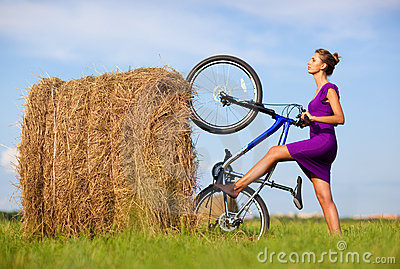 Young woman with bicycle at the field
