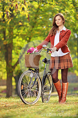 Young woman with a bicycle in a park
