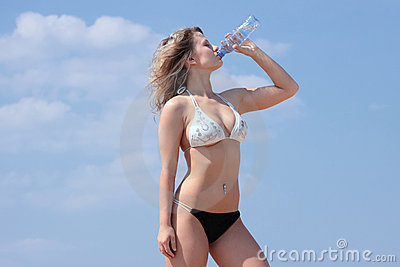 Young woman in bikini drinking water