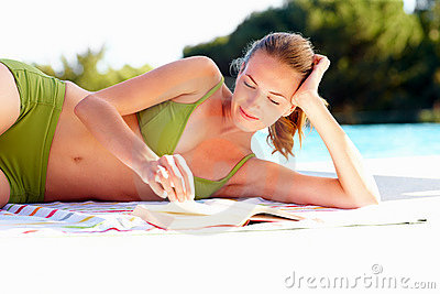 Young woman in bikini reading a book by a pool
