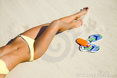 Young woman in bikini sunning on the beach