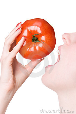 Young woman biting tomato