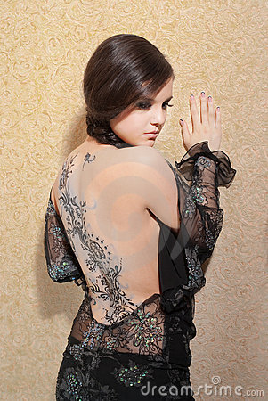 Young woman in black dress with body art