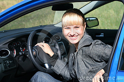 Young woman in a blue car