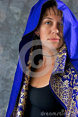 Young woman in blue and gold cape
