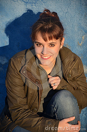 Young woman on a blue wall