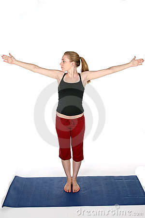 Young woman on blue yoga mat with arms out