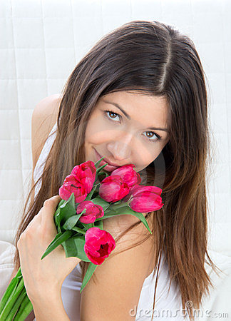 Young woman with bouquet of red tulips flowers