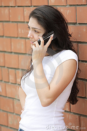 Young woman at brick wall talking cellphone