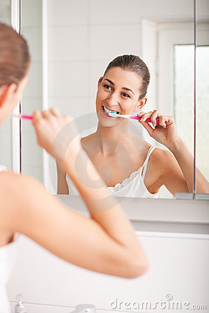 Young woman brushing her teeth in front of a mirro