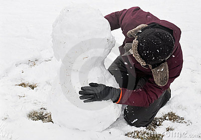 Young woman building snowman
