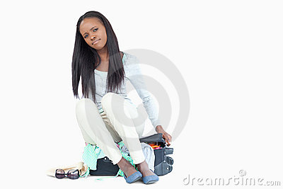 Young woman can t get her suitcase closed