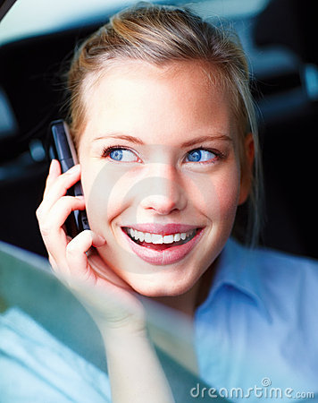 Young woman in a car talking on mobile phone
