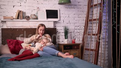 Young woman caressing her daughter to fall asleep stock video footage