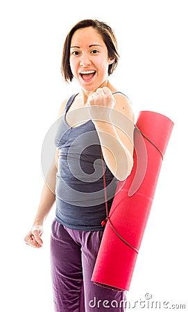 Young woman carrying exercise mat celebrating success