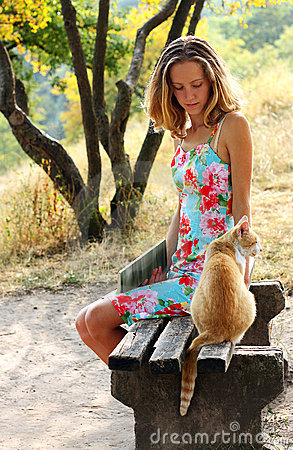 Young woman and a cat sitting on the bench