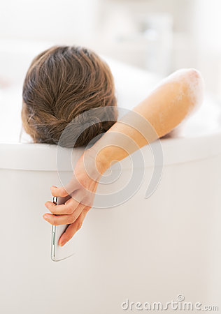 Young woman with cell phone laying in bathtub